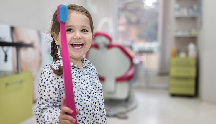 ovely toddler visiting the dentist, having an examination.