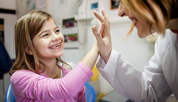 girl giving dentist high five
