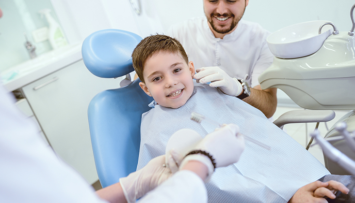 dentist showing young boy how to properly brush teeth