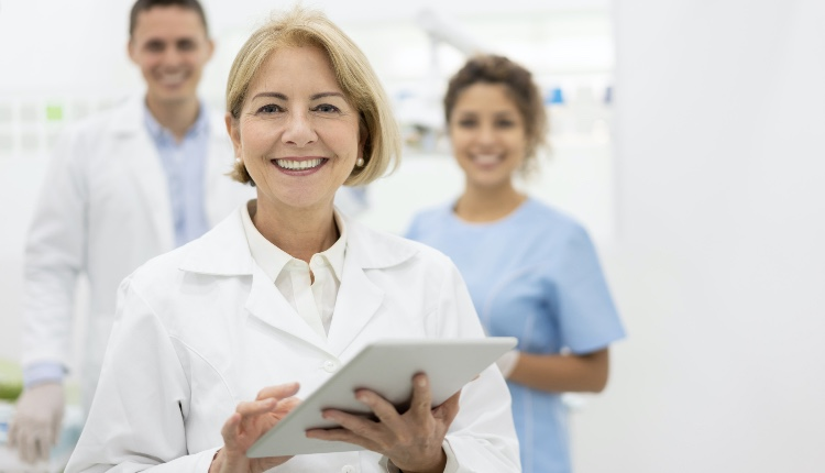 Happy dentist at the office with her team and holding a tablet computer