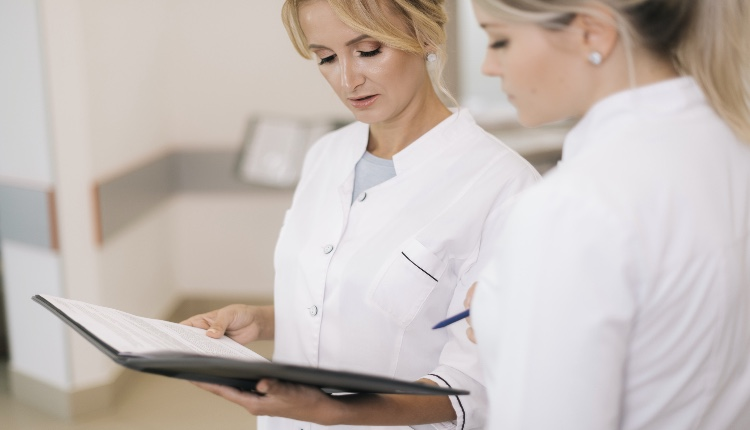 Two women doctors standing with clipboard at hospital and discussing cases