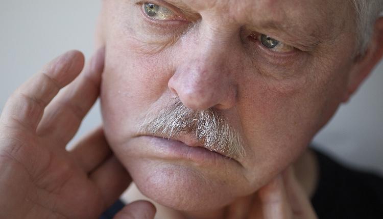 Senior man touches his sore jaw area.