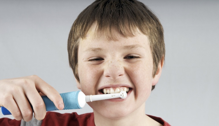 Boy aged 12 to 13 years brushing teeth with electric toothbrush