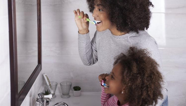 Mother and daughter are brushing their teeth in the bathroom
