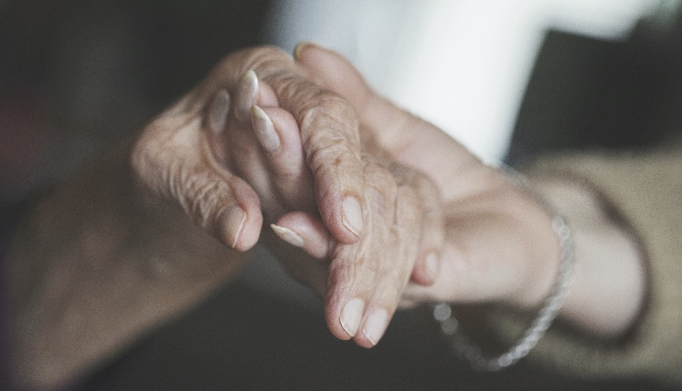 home caregiver holding hand of very old woman