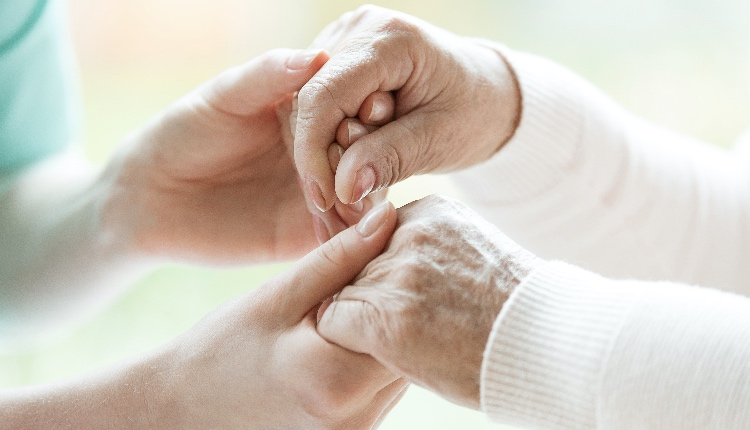 hoto with close-up of caregiver and patient holding hands