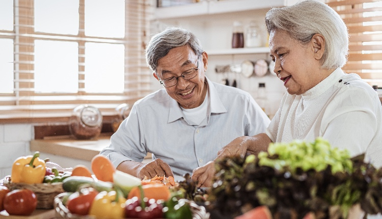 Senior asian couple cooking together in kitchen