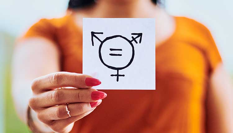 Cropped shot of unrecognizable woman holding a piece of paper with gender equality symbols outdoors