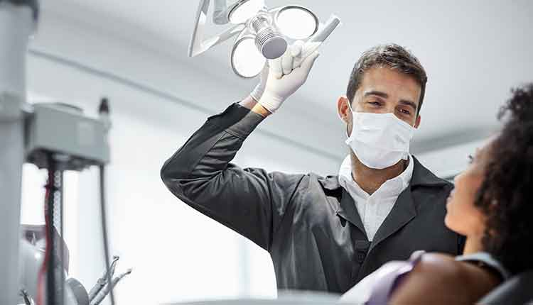 Dentist adjusting surgical light in dental clinic