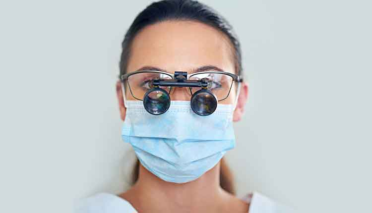 Portrait of a young female dentist wearing magnifying glasses