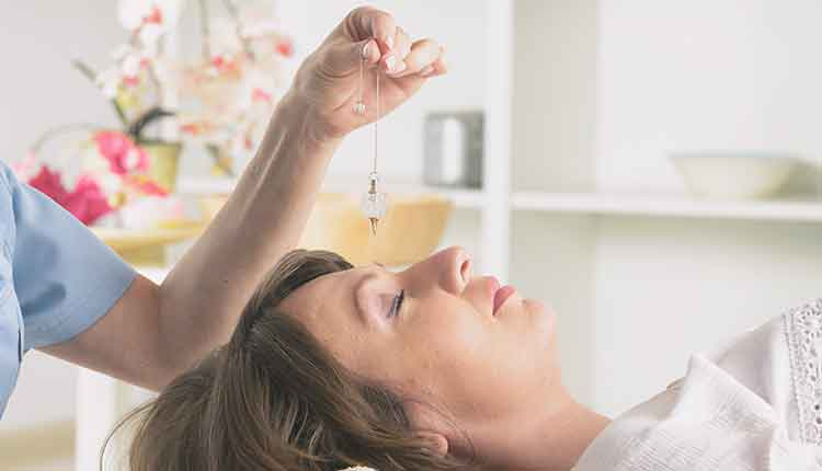 Therapist using pendulum to make a diagnosis