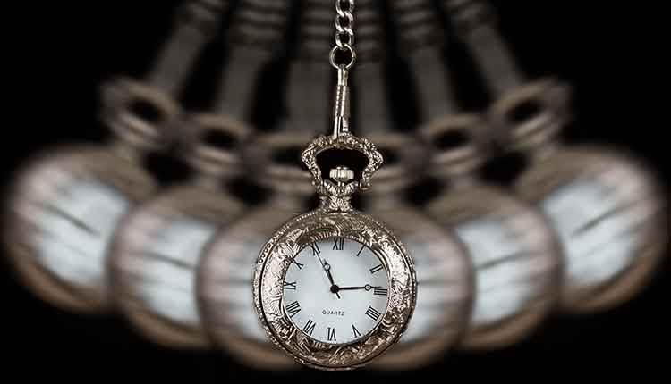 Pocket watch silver swinging on a chain black background to hypnotize