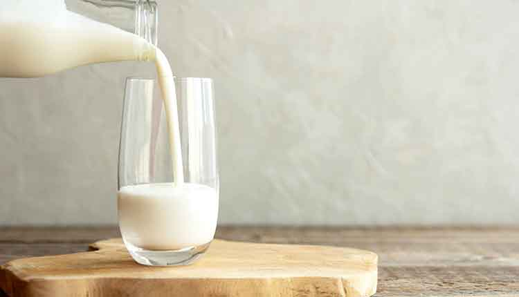 Kefir, milk or Turkish Ayran drink are poured into a glass cup from a bottle.