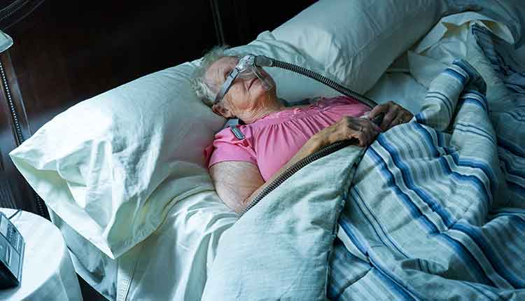 elderly woman in bed with cpap machine