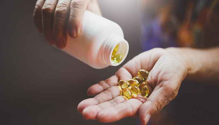 person pouring yellow pills into her hand