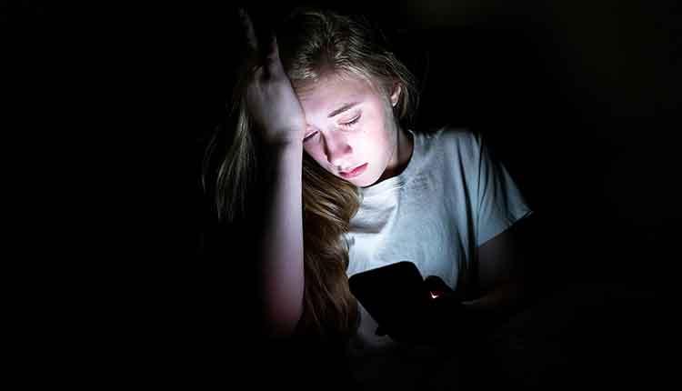 girl upset, on her phone in the dark