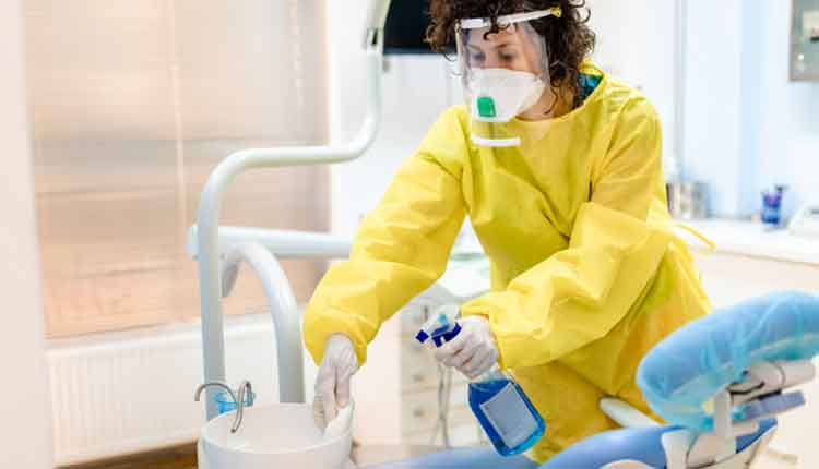 Dentist assistant using strong disinfectant agent to clean dental office for the next patient