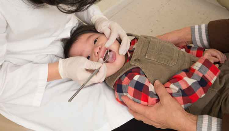1 Year old's first dentist appointment. This is the proper position for a baby's dental check-up - baby's head is in dentist's lap knee-to-knee with mom who is holding on.