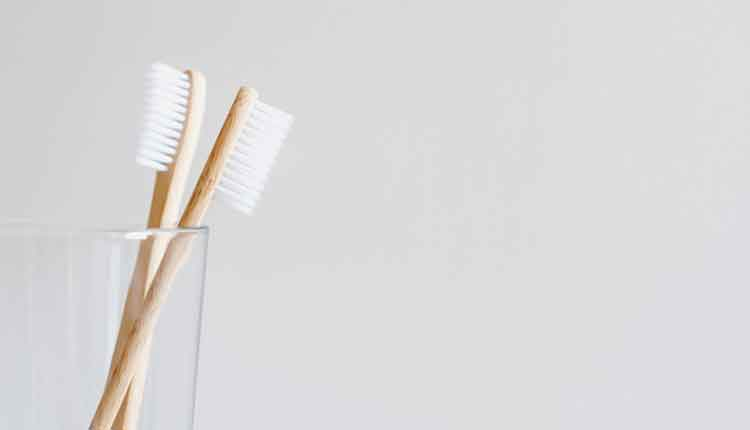 Stylish natural eco friendly toothbrushes with wooden bamboo handle in glass on white background. Oral hygiene concept. Copy space. Reduce plastic waste, sustainable lifestyle.