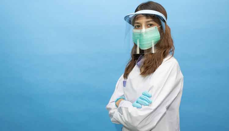 Beautiful dentist wearing surgical mask and face shield. The letter on her gown is her name written in Thai alphabets.