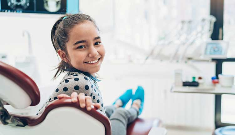 young girl at dentist smiling